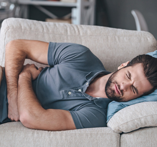 Man lying on couch and holding stomach in pain